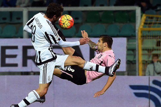PALERMO, ITALY - NOVEMBER 29: Aleksandar Trajkovski (R) of Palermo kicks the ball as Claudio Marchisio tackles during the Serie A match between US Citta di Palermo and Juventus FC at Stadio Renzo Barbera on November 29, 2015 in Palermo, Italy.  (Photo by Tullio M. Puglia/Getty Images)